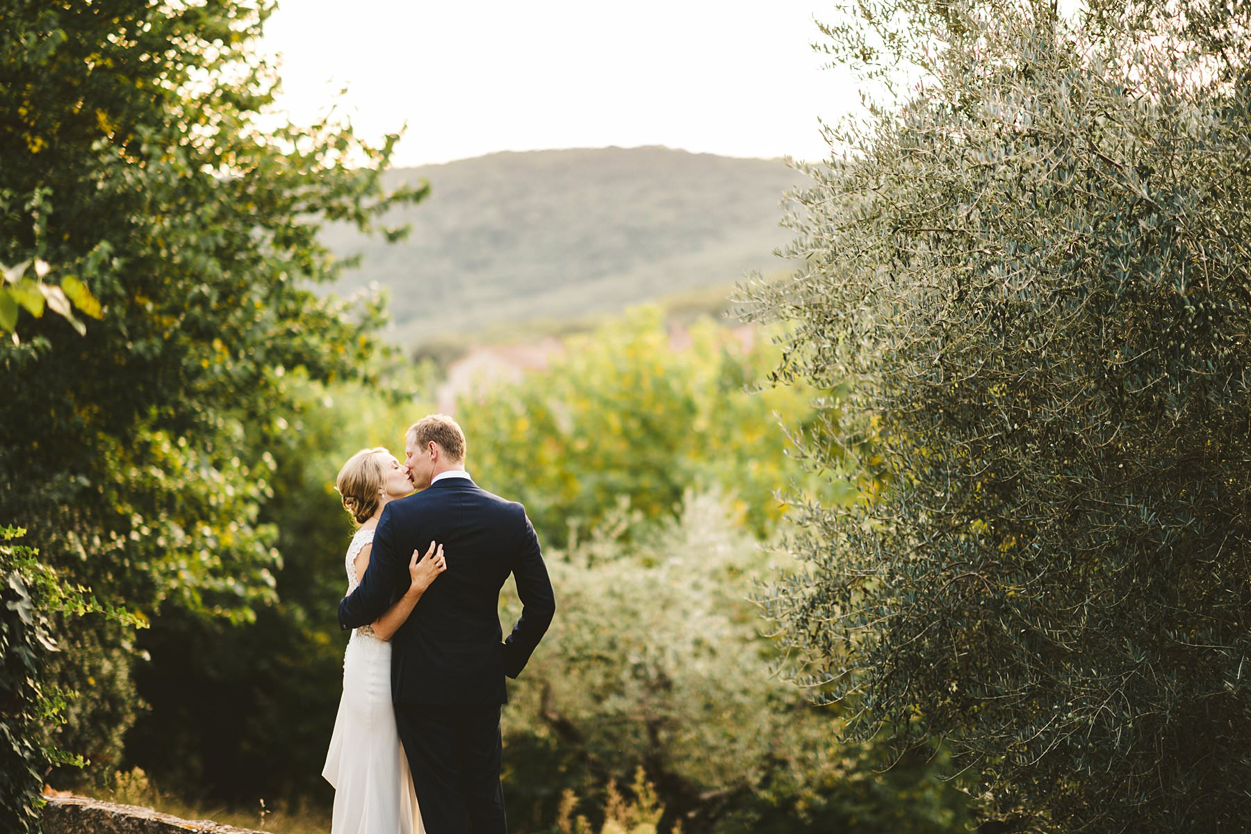 A special international wedding in the countryside of Umbria, Italy. Beautiful and elegant Australian dreaming couple portrait around the property of Villa Monte Solare, a historic residence tucked in the countryside among rolling hills. The settings were countryside landscapes with cypress lines, olive groves and a stunning wall covered in red ivy leaves