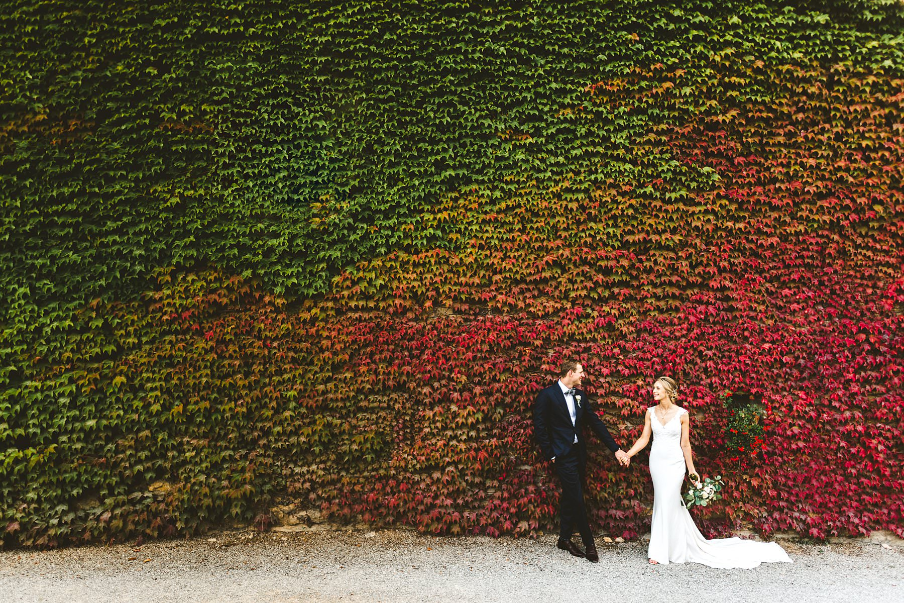 A special international wedding in the countryside of Umbria, Italy. This beautiful Australian couple dreamed this unforgettable day for a long time and finally they made it. Bride and groom portrait at stunning wall covered in red ivy leaves near Villa Monte Solare, a historic residence tucked in the countryside among rolling hills