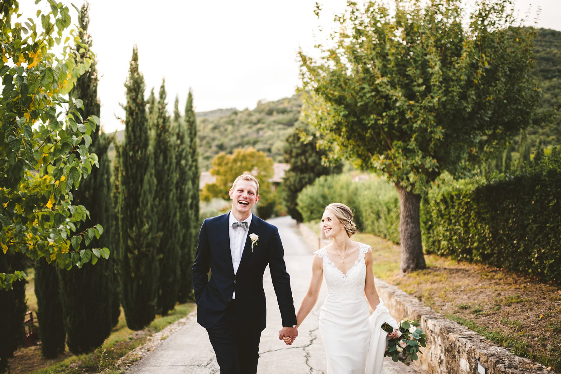 A special international wedding in the countryside of Umbria, Italy. Elegant Australian wedding smiling couple portrait around the property of Villa Monte Solare, a historic residence tucked in the countryside among rolling hills. The settings were countryside landscapes with cypress lines, olive groves and a stunning wall covered in red ivy leaves