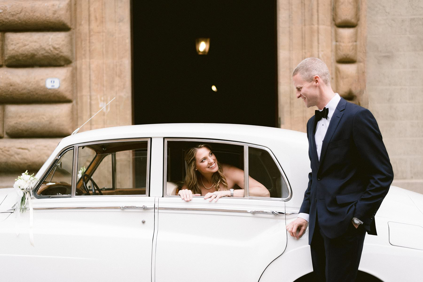 Intimate exquisite wedding in the heart of Florence, Italy. Bride and groom wedding portrait with vintage Rolls Royce car near Palazzo Gondi near Palazzo Vecchio in the very heart of Florence