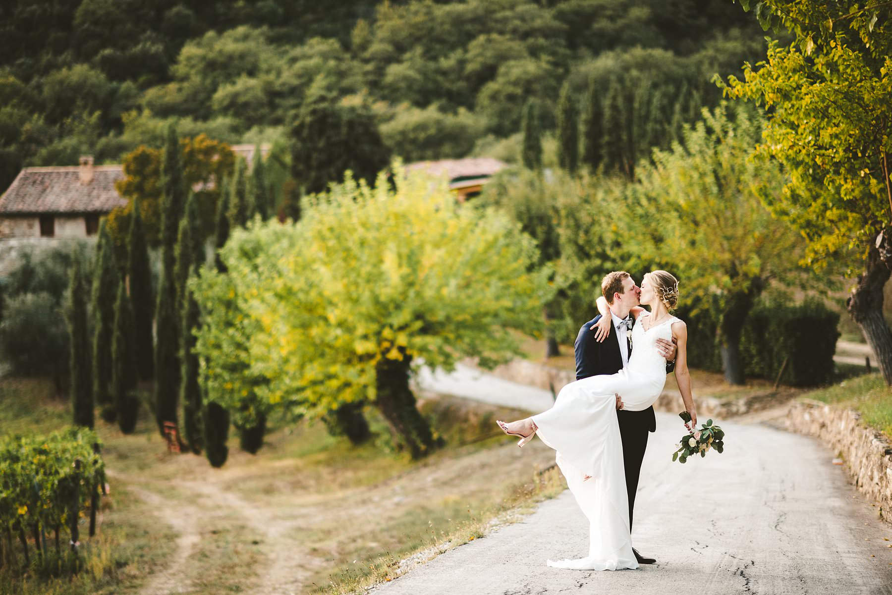 Getting married in the Italian countryside. Elegant Australian wedding couple portrait around the property of Villa Monte Solare, a historic residence tucked in the countryside among rolling hills. The settings were countryside landscapes with cypress lines, olive groves and a stunning wall covered in red ivy leaves