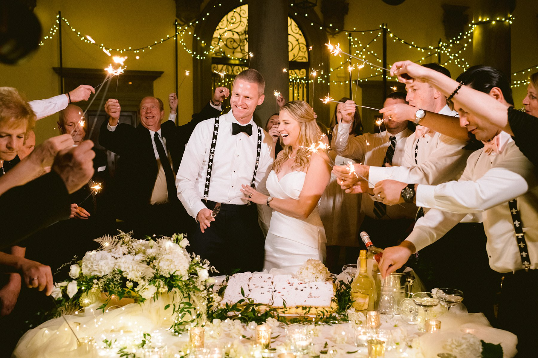 Beth and Evan's exquisite intimate and luxury wedding: just like a dream. Cake of the cut with guests and sparkle lights at Palazzo Gondi courtyard
