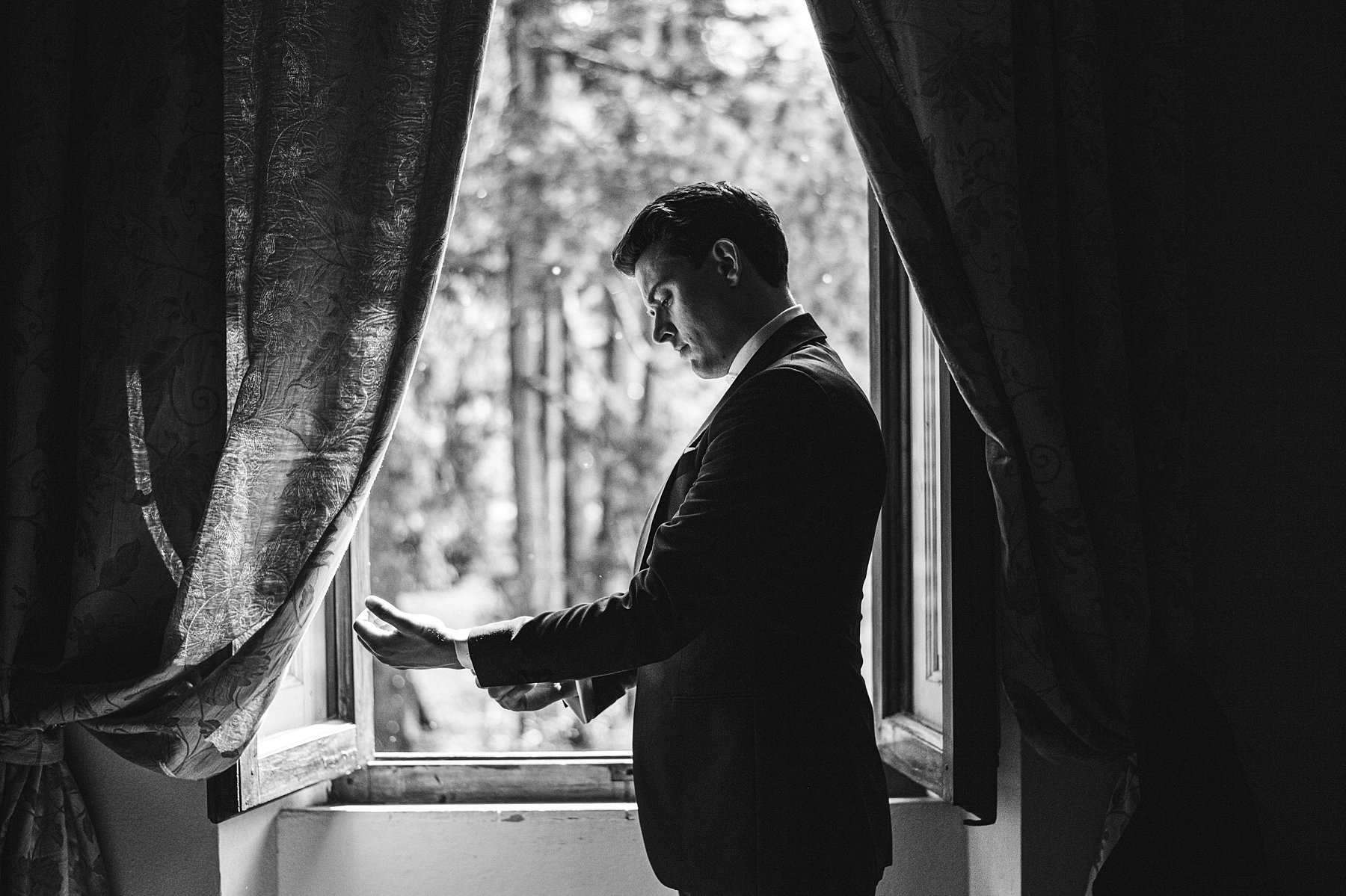 Heartfelt small wedding in the countryside of Tuscany. Elegant wedding photo with the groom during his preparation at Palazzo Vanneschi in Bucine Valdarno, a stone building from the 17th century immersed in a luxuriant park