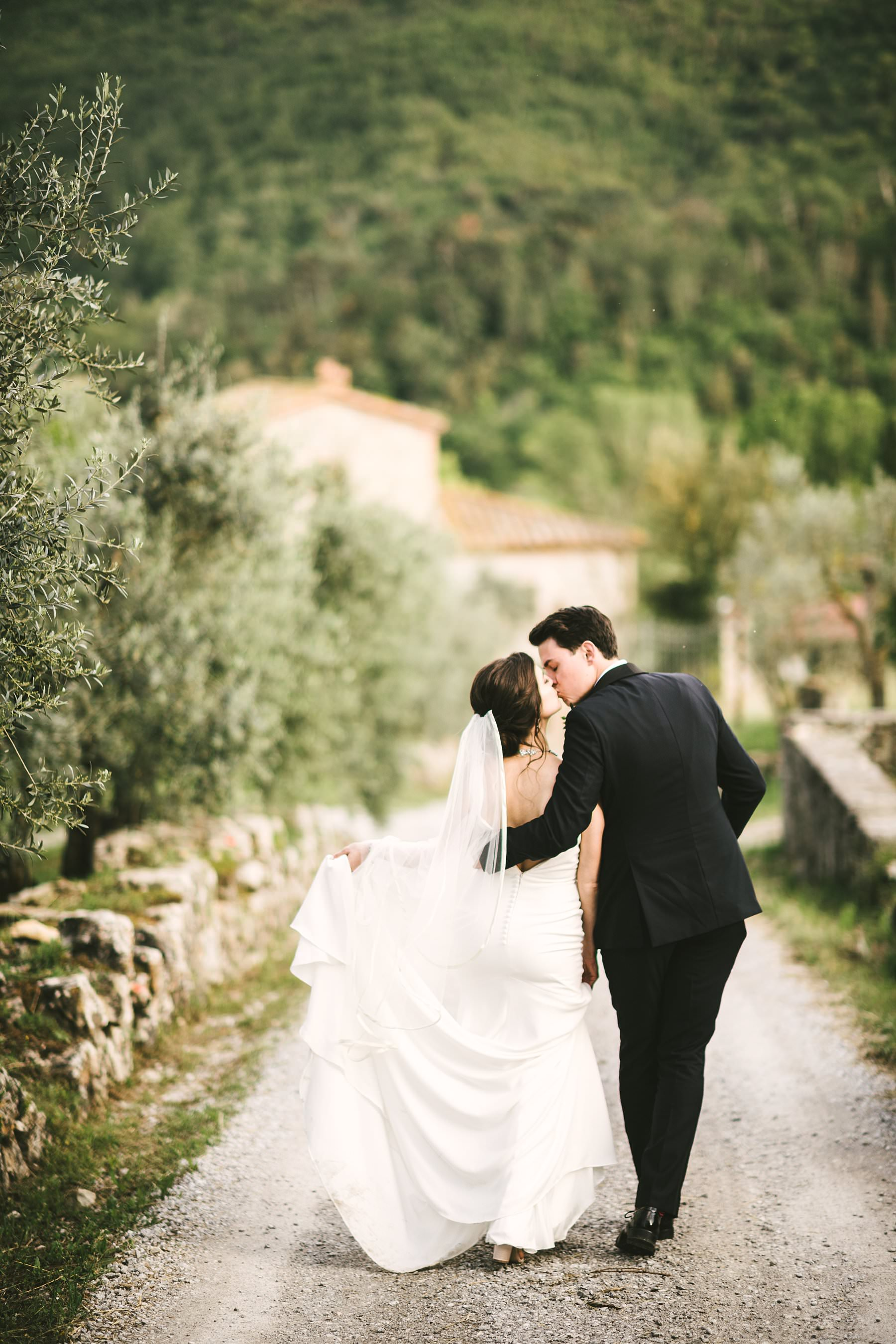 Heartfelt small wedding in the countryside of Tuscany. Lovely and elegant bride and groom portrait session in a white street in the countryside of Tuscany near Palazzo Vanneschi in Bucine