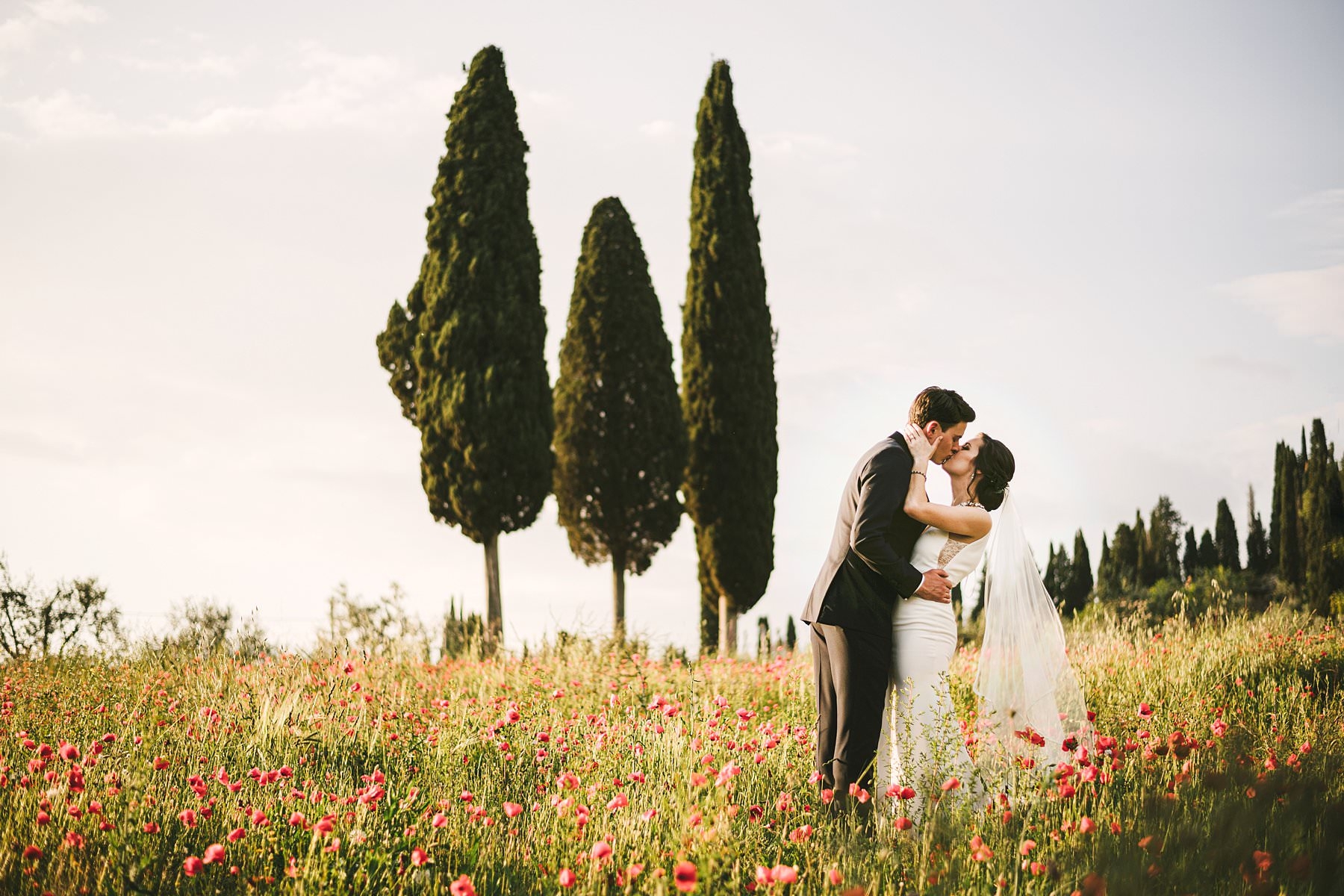 Heartfelt small wedding in the countryside of Tuscany. In the end of bride and groom portrait session, it was finally time for another wish to be granted: Katrina was longing for a countryside photoshoot in a field of poppies. We found the perfect spot among the hills of Valdarno: an immense expanse of bright red poppies on a golden field, with cypresses on the background. There couldn't have been a most romantic setting for those strongly desired photographs, that Katrina and John will treasure forever