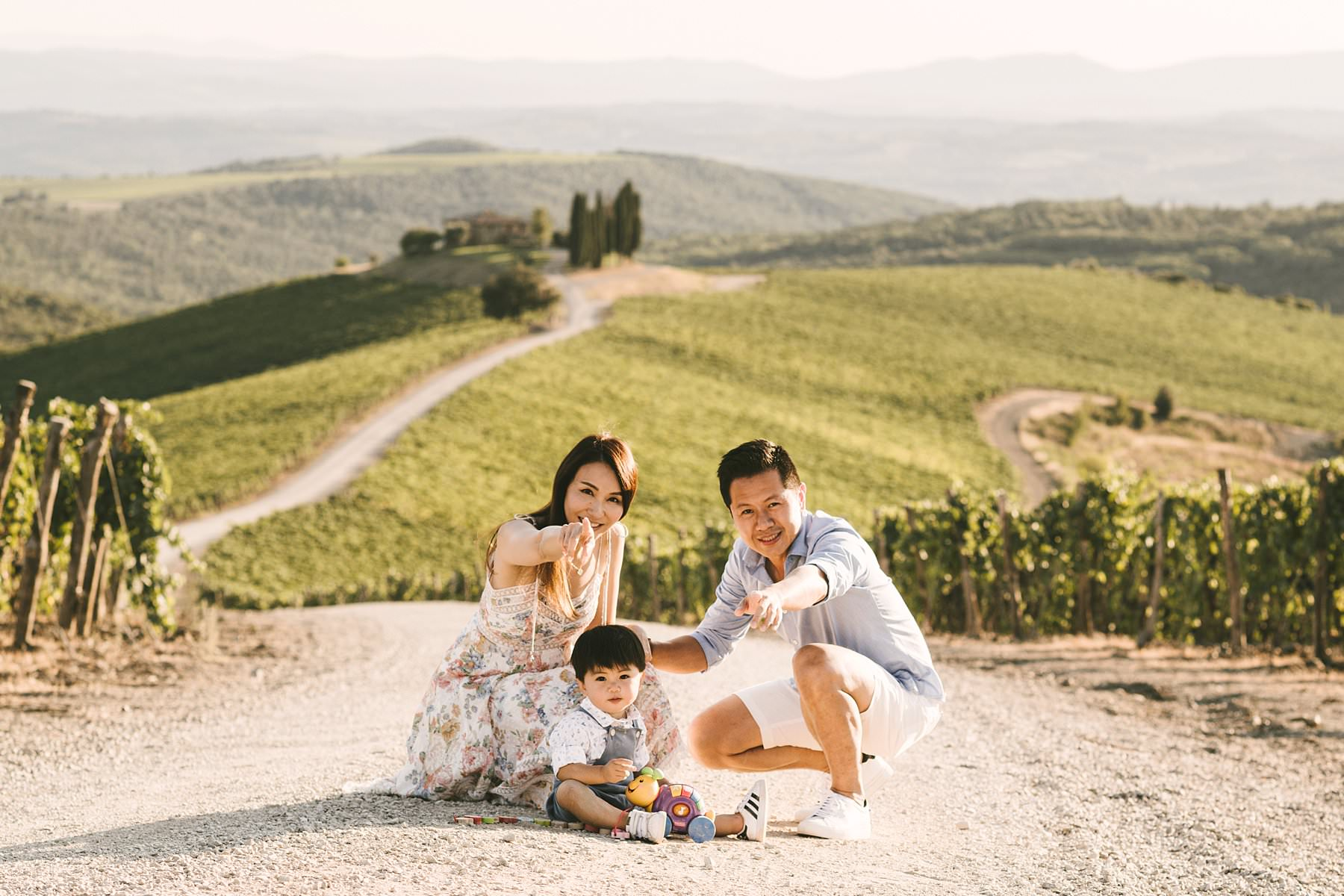 "Sweet family holiday photoshoot in the wonderful Tuscan countryside. Serena and Kelvin, wife and husband from Singapore, chose Tuscany as the destination of a relaxing holiday with their littlest love: their son. Since he was so young, they decided to contact me for a family holiday photoshoot so that the memory of those days would live forever – for all of them. Italy offers a ton of incredibly beautiful places to visit on your next vacation, and Tuscany provides some of the most splendid settings for an emotional family holiday photoshoot. Rosewood Castiglion del Bosco is definitely one of those: with its 5000-acre estate tucked in the heart of Val d'Orcia, this ancient and perfectly preserved hamlet will make you live a one-of-a-kind experience. When I shot Serena and Kelvin's family photos, the owners were so kind to open their private ""Capanna"" vineyard for us. Imagine an endless expanse of rolling hills covered in grapevines, with a white path that guides your gaze to a little, picturesque cypress grove. The warm and golden light of the late afternoon was the finishing touch to a family holiday photoshoot that they will surely cherish forever"