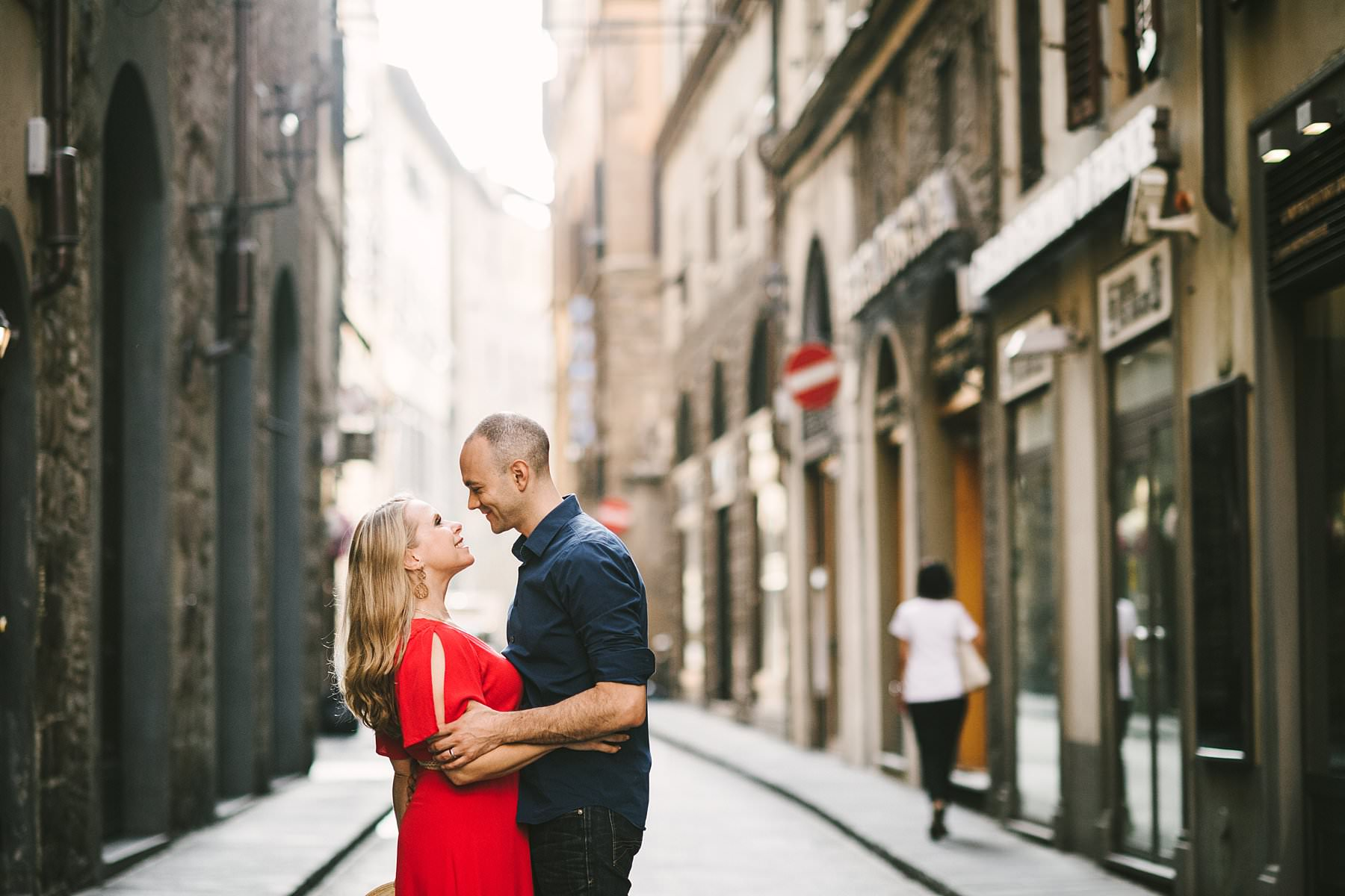 Anniversary photos in Florence: soft as sunrise, red as passion. Lovely couple portrait in the streets of Florence near Palazzo Vecchio and Piazza della Signoria