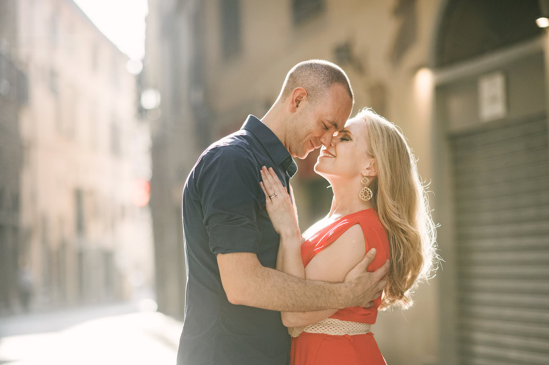 Anniversary photos in Florence: soft as sunrise, red as passion. Lovely couple portrait in the streets of Florence near Palazzo Vecchio and Piazza della Signoria under a gorgeous delicate and warm light