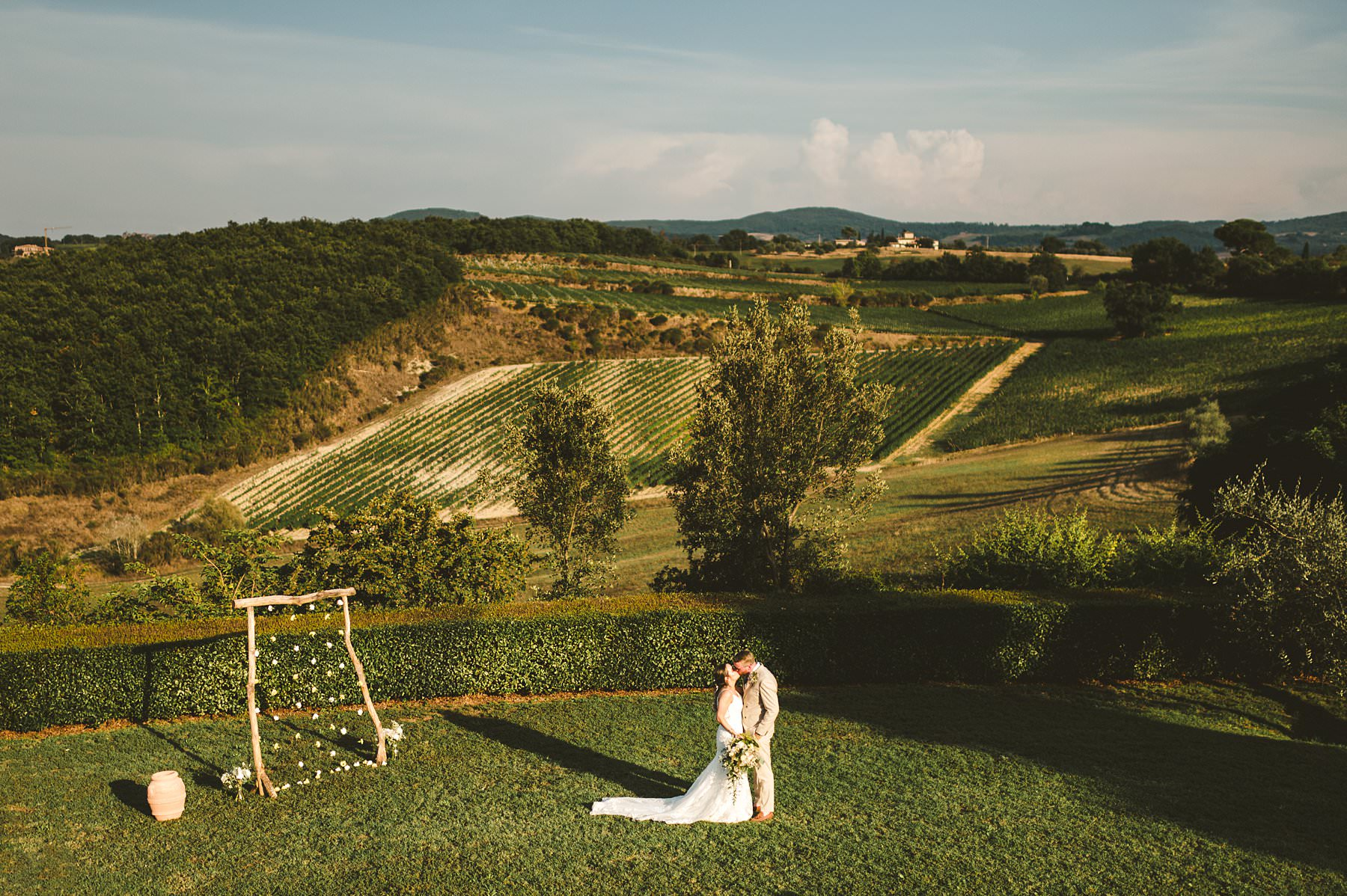 A dreamy small wedding abroad, at Villa Boscarello in Val D'Orcia. Lovely bride and groom portrait with the green rolling hills of Tuscany countryside as background