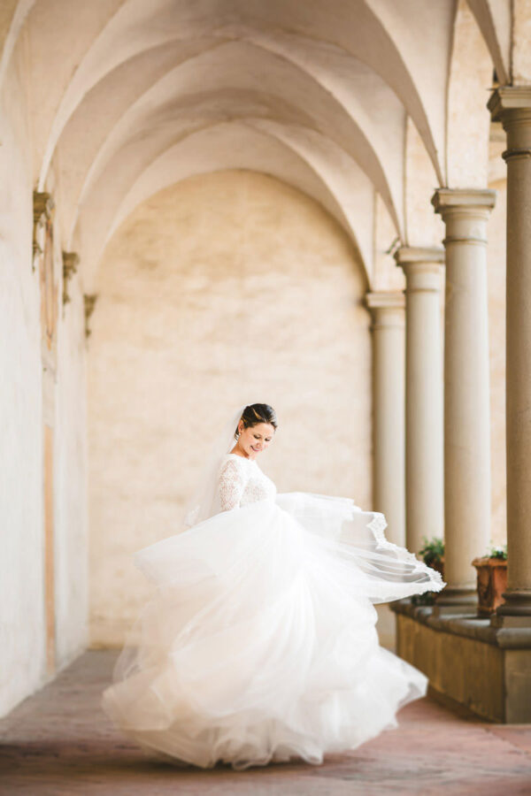 Beautiful and amazing bride in Atelier Eme wedding dress under the archway of Certosa di Firenze church