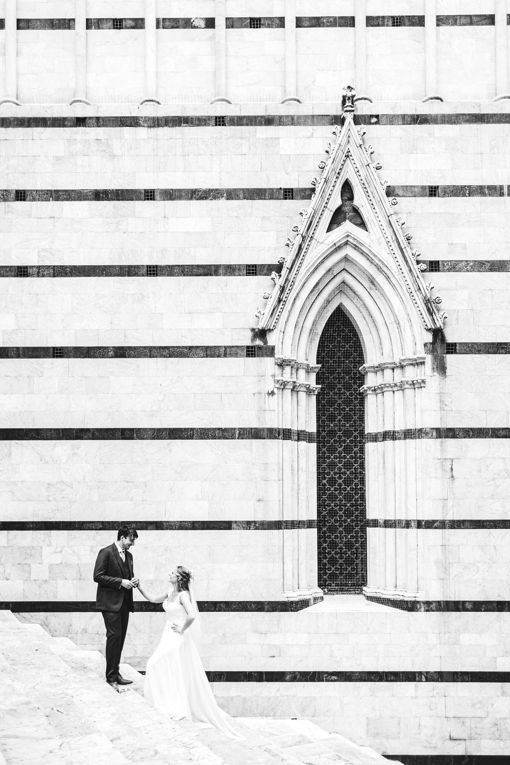 Getting married in Italy, surrounded by beauty. Bride Poppy and groom Chris elopement photo near the Duomo of Siena, Tuscany