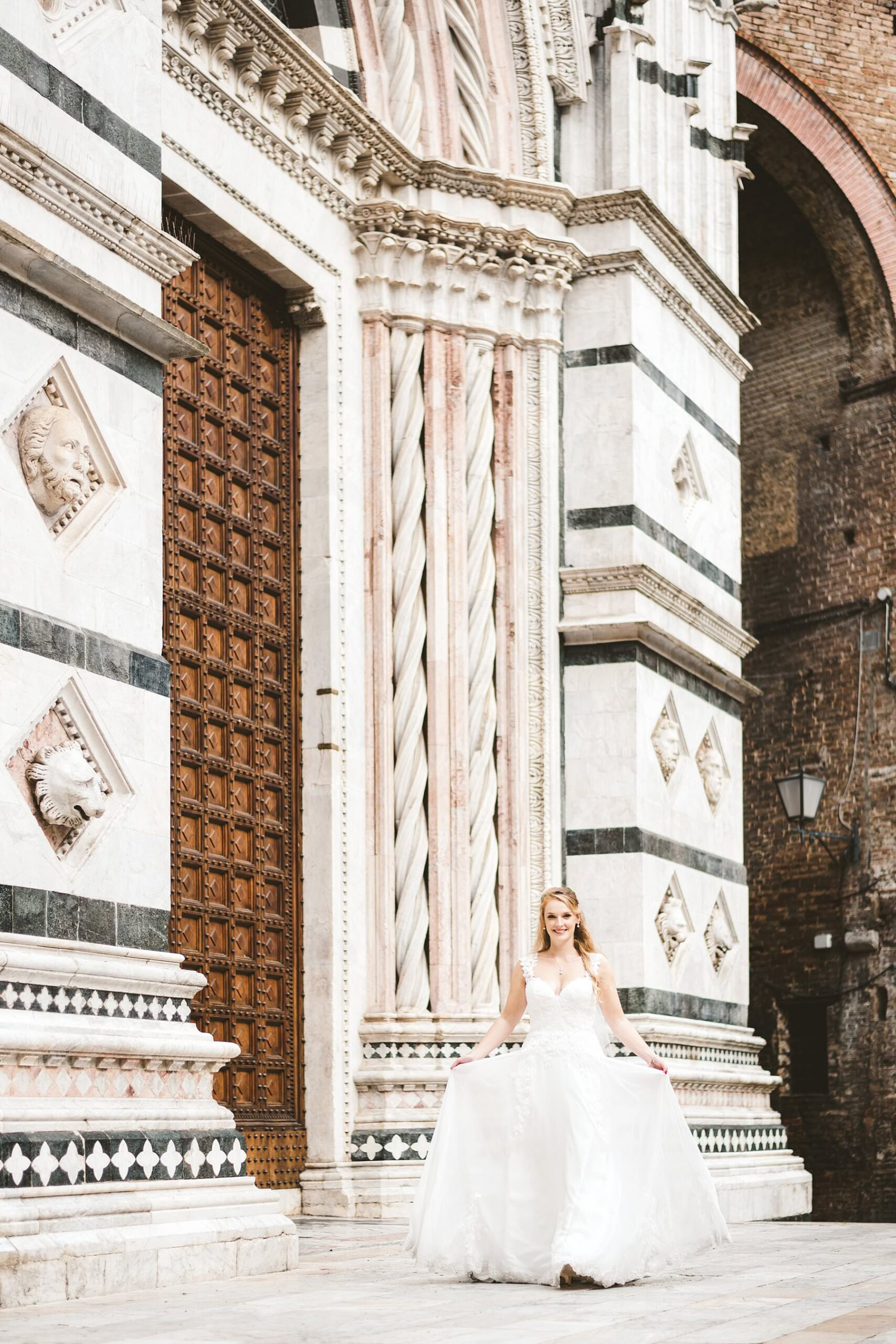 Elegant bride in gorgeous Justin Alexander gown walks near the Duomo of Siena in the heart of the city. Intimate destination wedding elopement in Italy