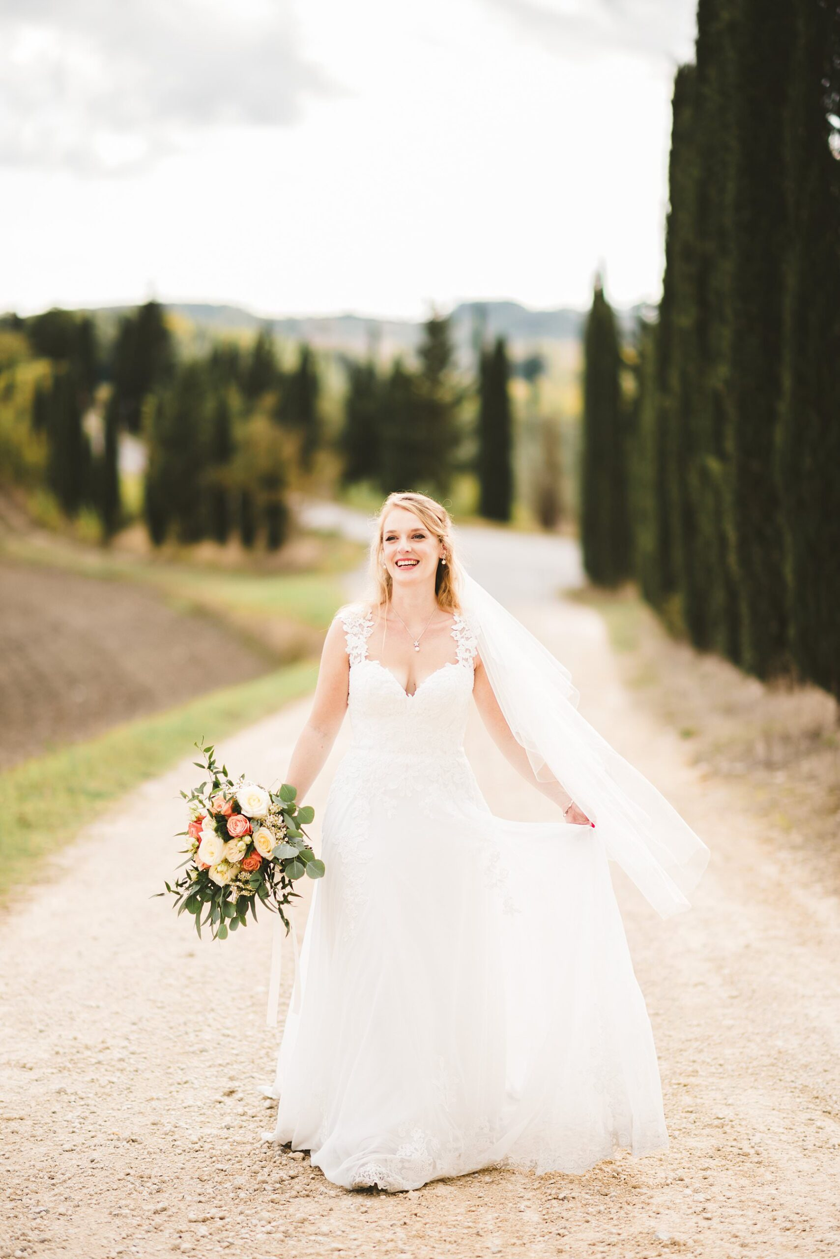 Lovely smiling bride Poppy in her Justin Alexander white wedding gown walks in the evocative cypresses road in the countryside of Siena, Tuscany