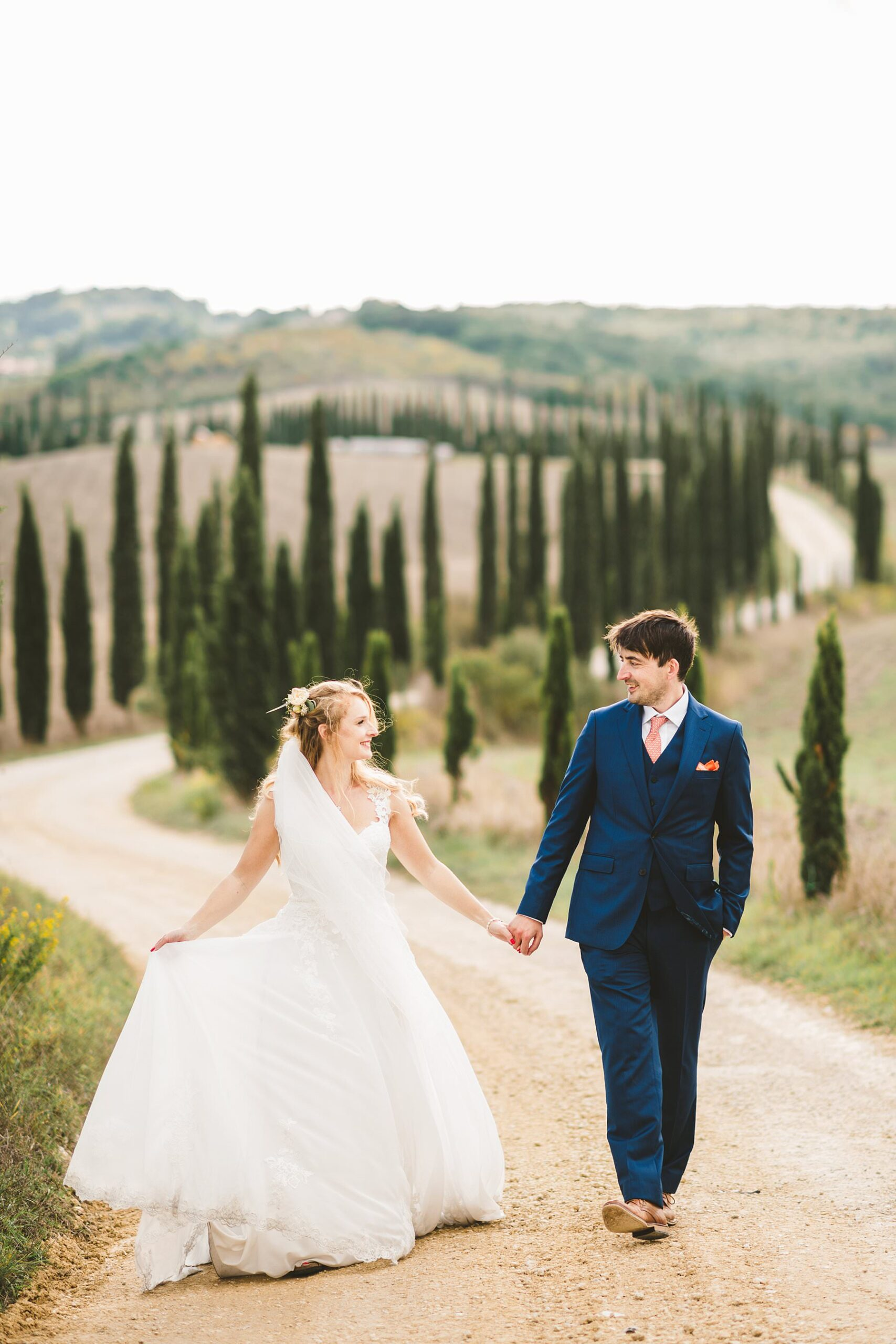Destination elopement wedding in Tuscany. Bride and groom portrait walk tour surrounded by the stunning countryside views and cypresses road