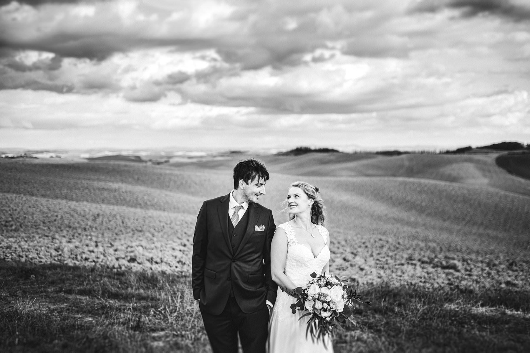Destination intimate elopement wedding in Tuscany countryside. Bride and groom portrait with gorgeous rolling hills as background