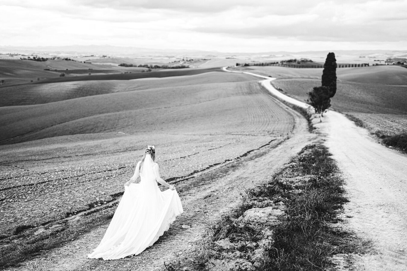 Gorgeous real bride in gorgeous Justine Alexander gown walks toward the evocative and iconic countryside of Tuscany near Siena