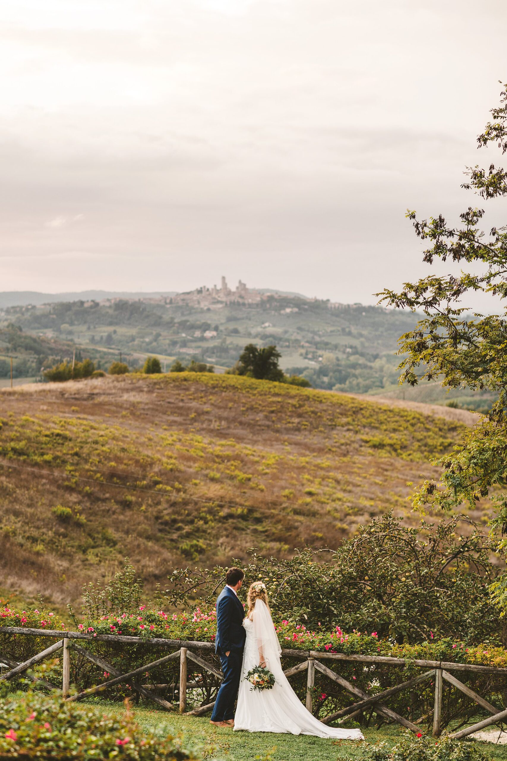 Bride and groom look at the splendid Tuscan countryside view with evocative rolling hills