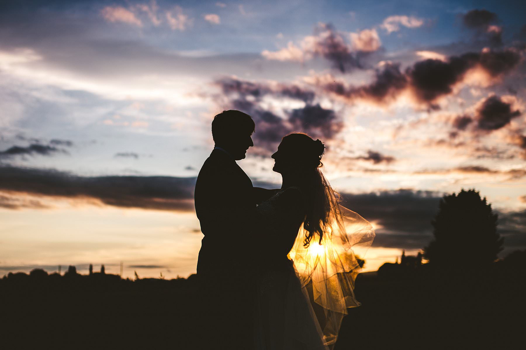 Gorgeous sunset elopement photo with bride and groom in the countryside of Tuscany near Taverna di Bibbiano